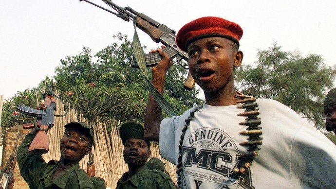 Young soldiers from a Ugandan supported Congolese rebel movement group, sing liberation songs waving their rifles in this photo in the north eastern Congolese town of Bunia. (AP Photo/Karel Prinsloo)