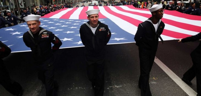 """NEW YORK, NY - NOVEMBER 11: Members of the U.S. Navy march with the American Flag in the the nation's largest Veterans Day Parade in New York City on November 11, 2015 in New York City. Known as """"America's Parade"""" it features over 20,000 participants, including veterans of numerous eras, military units, businesses and high school bands and civic and youth groups. (Photo by Spencer Platt/Getty Images) (Credit: Getty Images / Spencer Platt)"""